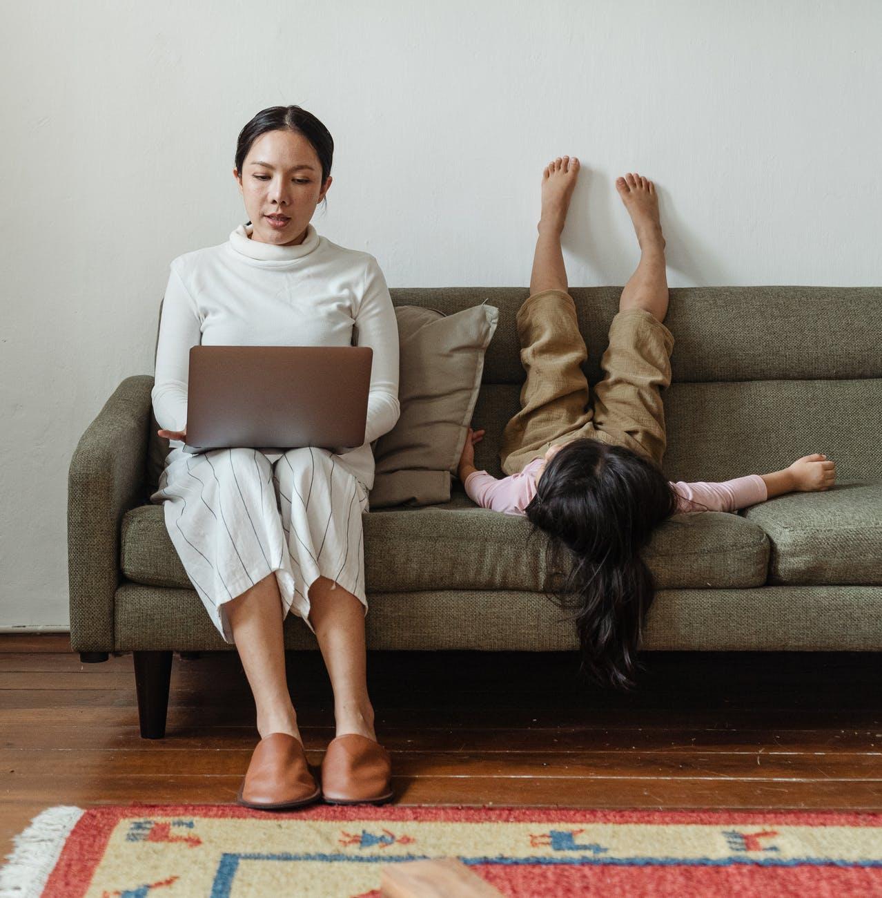kvinde som arbejder ved siden af sit barn